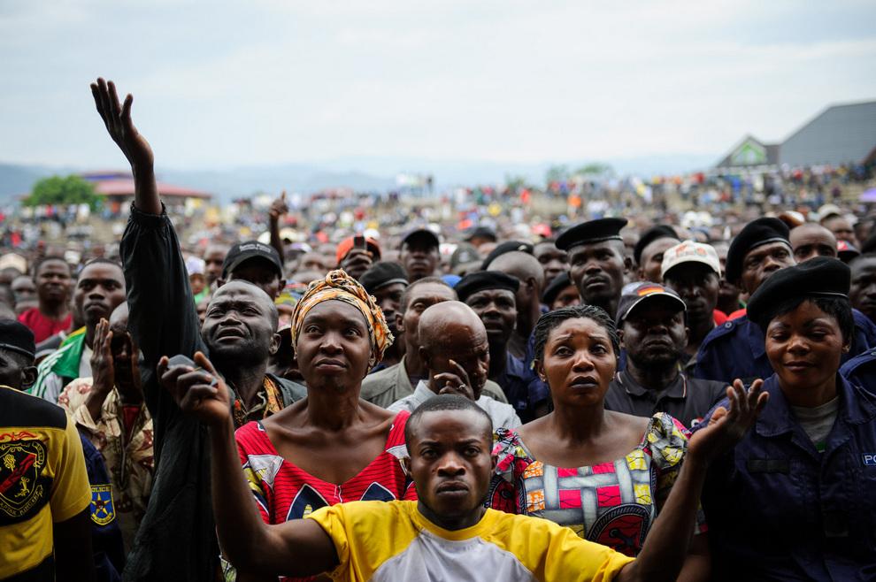 Жители Гомы, провинция Северное Киву, Конго, слушают оратора повстанцев, подполковника Вьянни Казараму (Vianney Kazarama). Большое собрание состоялось на стадионе «Вулканы», где мятежники потребовали от полиции и правительственных солдат сложить оружие и ответили на вопросы журналистов. (Phil Moore/GettyImages)