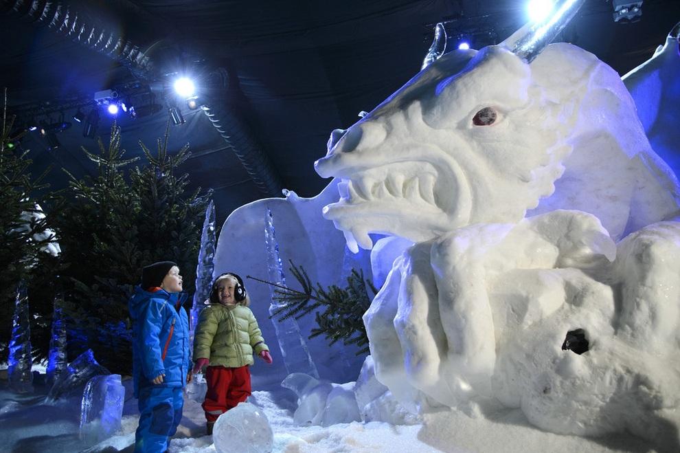 Дети стоят у снежного дракона на выставке «Магическое ледяное королевство», которая откроется в рамках ярмарки Winter Wonderland, Лондон, Англия. (Ben Pruchnie/Getty Images)