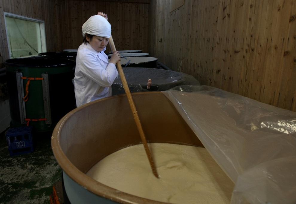 Шеф-повар Миса Каваиси (Misa Kawaisi) размешивает ферментированный рис на заводе «Надагику-Содзо», где варят сакэ, Химэдзи, префектура Хёго, Япония. (Buddhika Weerasinghe/Getty Images)
