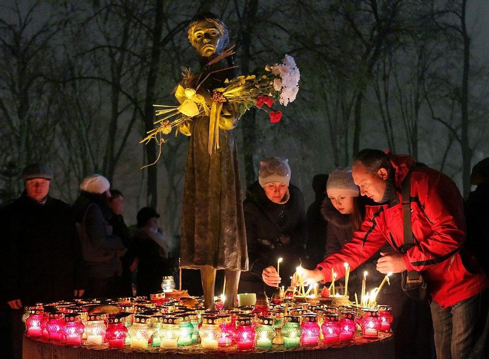Украинцы зажигают свечи у мемориала памяти жертв Голодомора в Киеве, Украина. (EPA/SERGEY DOLZHENKO)