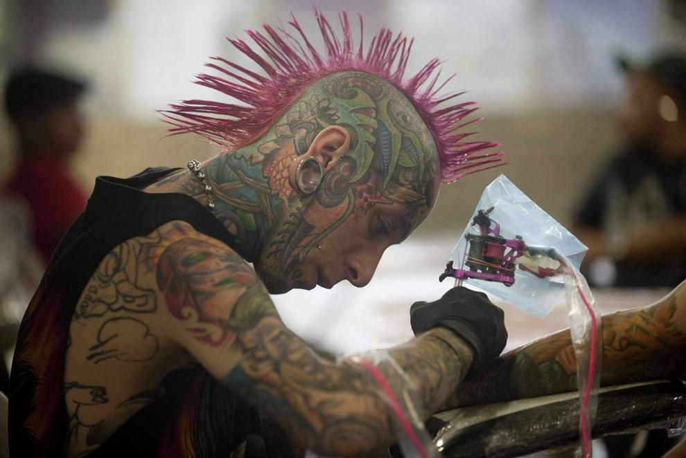 Эпатажный мастер с розовым ирокезом делает тату клиенту на Международном съезде любителей татуировок в Медельине, департамент Антиокия, Колумбия. (RAUL ARBOLEDA/AFP/Getty Images)