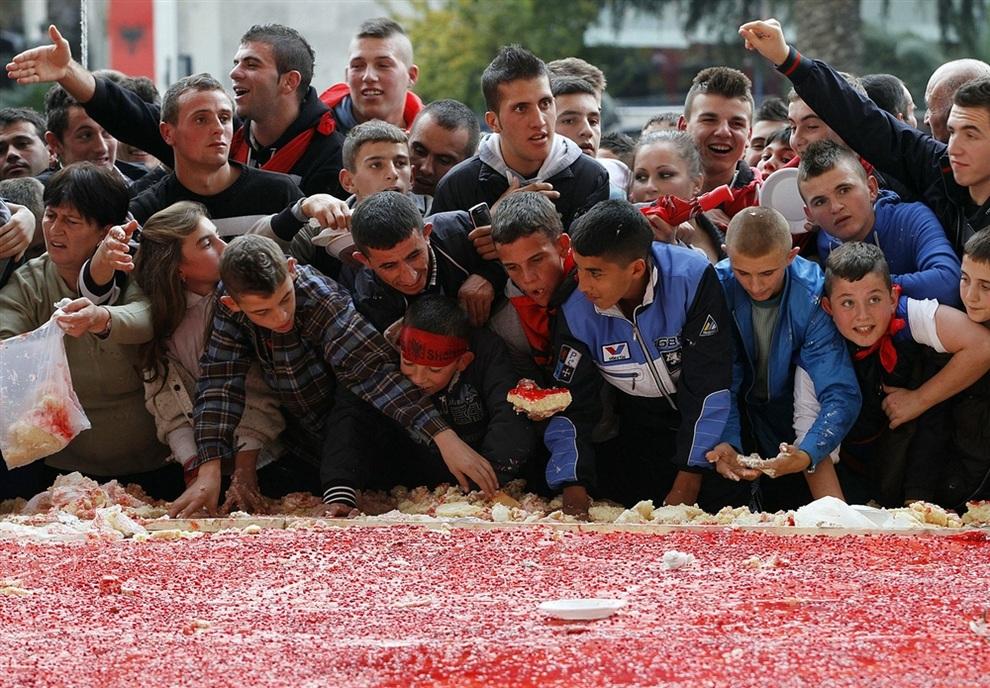 Подростки поедают огромный торт размерностью 550 кв. м, испеченный в честь 100-го Дня независимости и национального флага, Тирана, Албания. (REUTERS/Arben Celi)