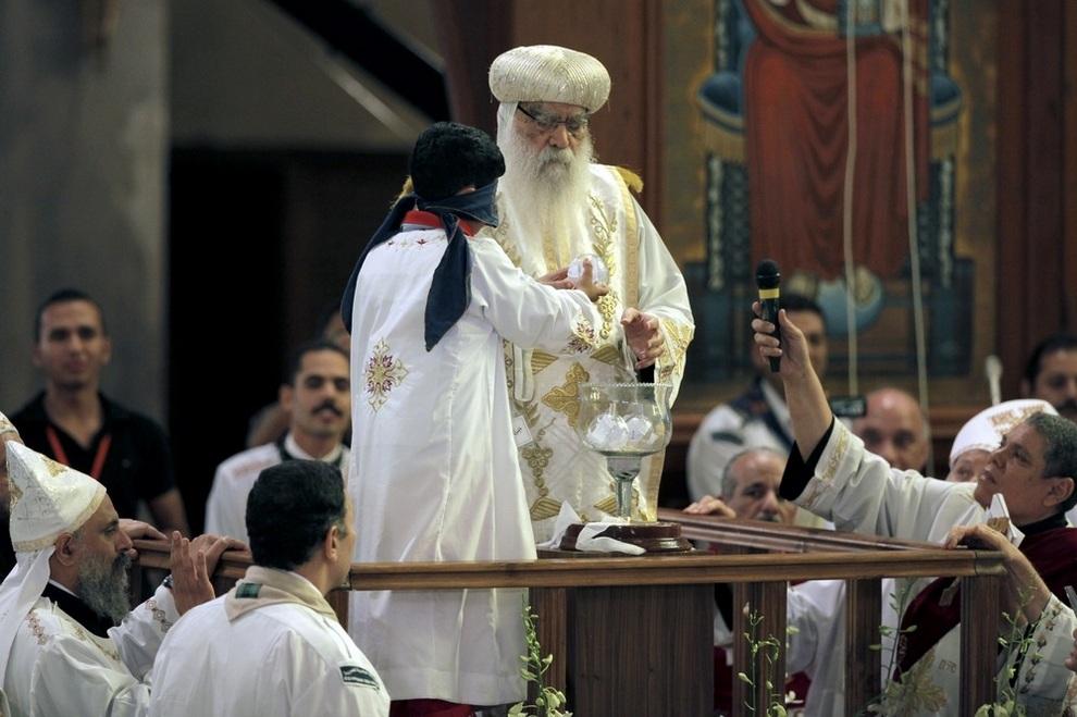 Ребёнок с завязанными глазами достает из чаши листок бумаги с именем нового патриарха Коптской православной церкви. Ему помогает временный «заместитель» Пахомий. (AP Photo/Nasser Nasser)