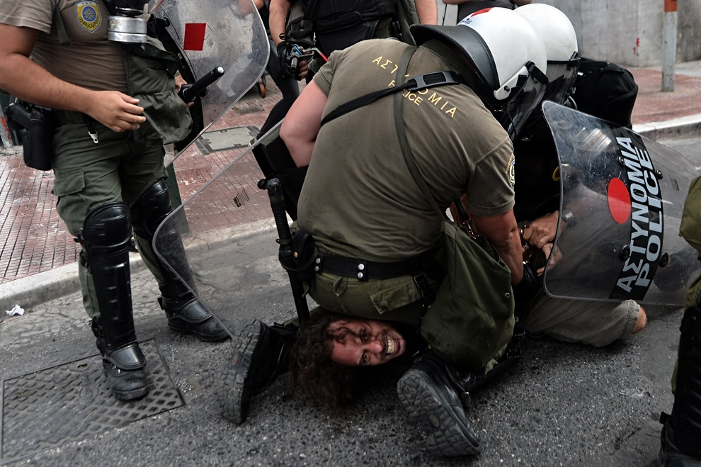Полиция задерживает особо буйного протестующего во время демонстрации в Афинах, Греция. (Aris Messinis/AFP/GettyImages)