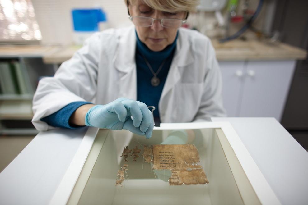 Аналитик Израильского управления древностей подготавливает фрагмент Кумранских рукописей в лаборатории для оцифровки, Иерусалим, Израиль. (Uriel Sinai/Getty Images)