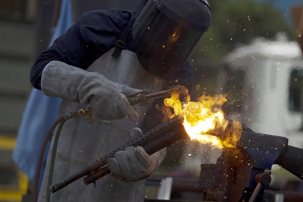 Рабочий уничтожает конфискованный дробовик во время общественного уничтожения оружия в Баркисимето, штат Лара, Венесуэла. (REUTERS/Carlos Garcia Rawlins)