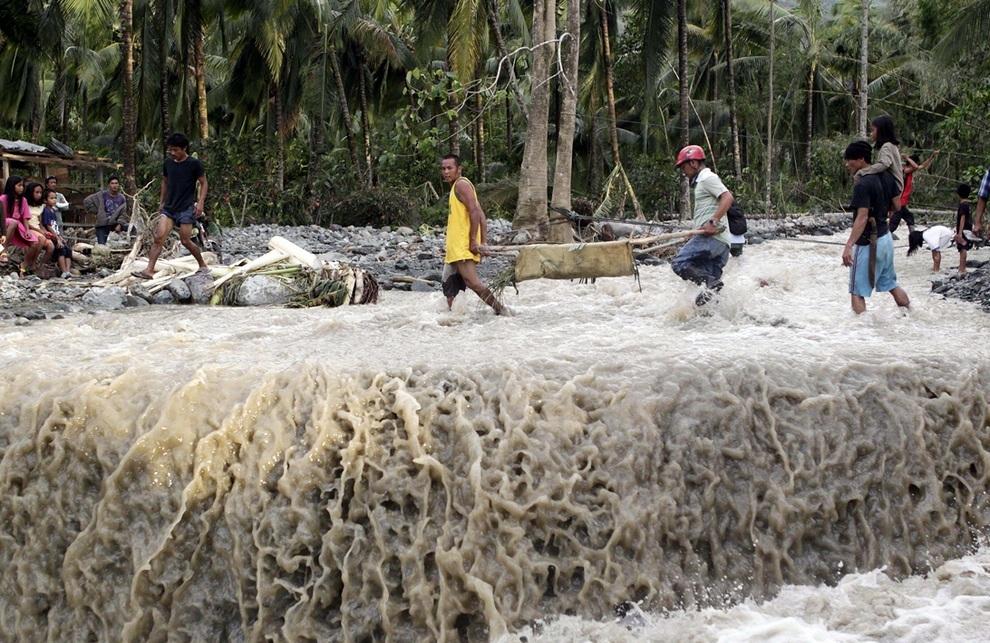 Местные жители несут тело погибшего после тайфуна «Бофа» в Новом Батаане, провинция Долина Компостела, Филиппины. (REUTERS/Erik De Castro)