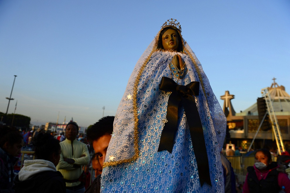 Паломник держит образ Девы Марии во время процессии у Храма Божьей Матери Гваделупской, Мехико, Мексика. (ALFREDO ESTRELLA/AFP/Getty Images)