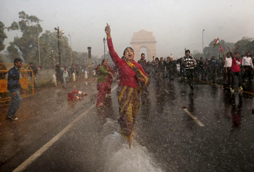 Женщина участвует в бурных демонстрациях за линчевание насильников, Нью-Дели, Индия, не смотря на попытки полиции буквально смыть митинг водой. (AP Photo/Kevin Frayer)