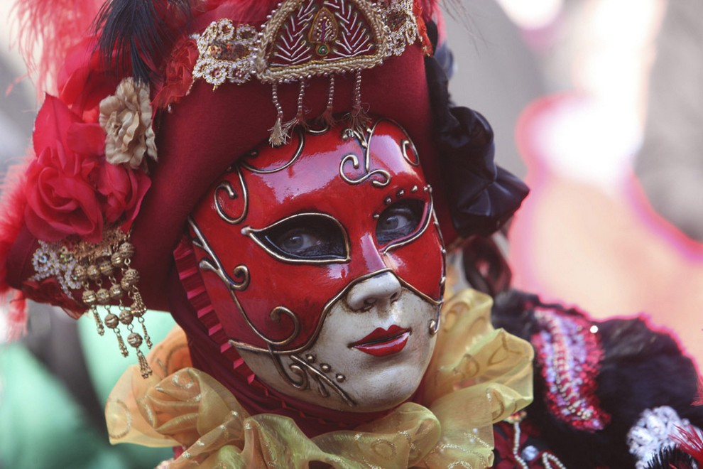 A woman dressed in traditional costume looks on during the Venetian Carnival in Saint Mark's square in Venice