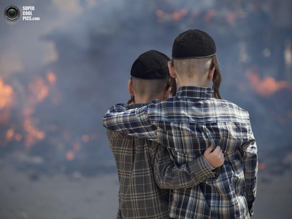 Два ультраортодоксальных еврейских мальчика наблюдают за сожжением хамеца, Бней-Брак, Тель-Авив, Израиль, 25 марта 2013 года. (AP Photo/Oded Balilty)