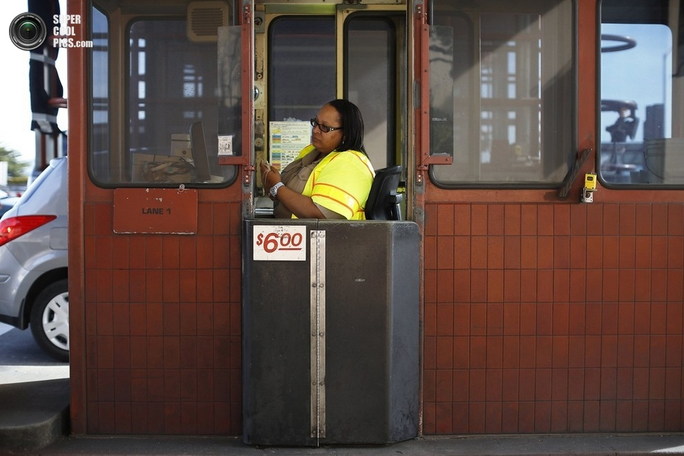 Сотрудница дорожной службы Джеки Дин (Jacquie Dean) ждёт оплаты за въезд на мост «Голден-Гейт», Сан-Франциско, штат Калифорния, США, 26 марта 2013 года. (REUTERS/Stephen Lam)