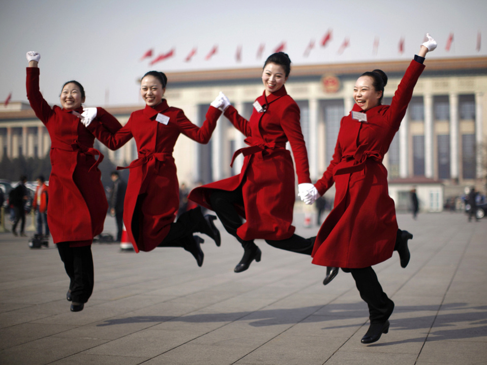 Hotel guides for delegates jump for a photograph outside the Great Hall of the People at Tiananmen Square during the opening ceremony of the National People's Congress in Beijing