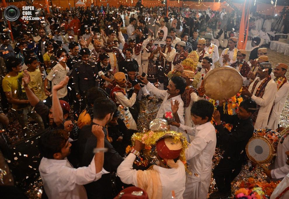 Танцующие женихи и члены их семей — здесь царит атмосфера праздника. (ASIF HASSAN/AFP/Getty Images)