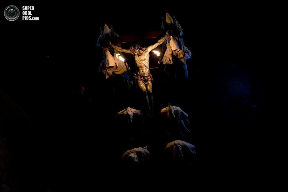 Кающиеся грешники несут пасо в виде распятия. (AP Photo/Daniel Ochoa de Olza)