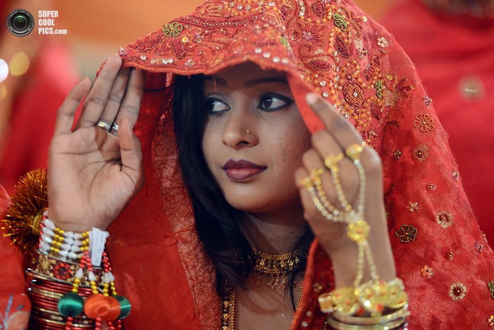 Одна из невест с любопытством рассматривает «подруг» по свадьбе, Карачи, Пакистан. (ASIF HASSAN/AFP/Getty Images)