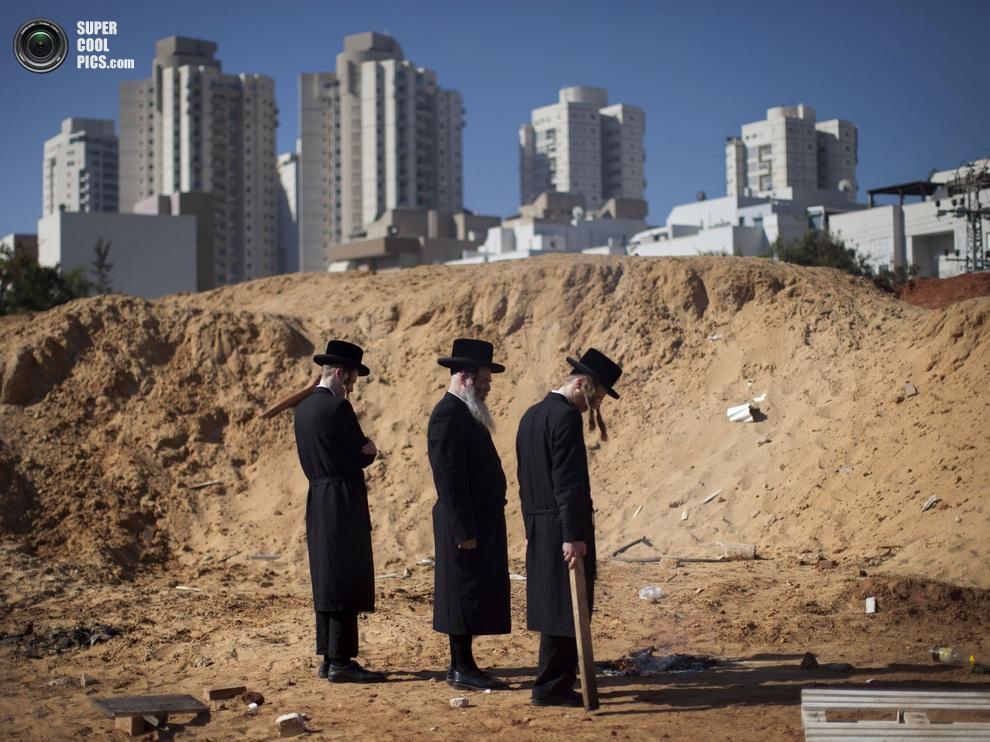 Три ультраортодокса, вооружившись палкой, наблюдают за тлением продуктов. (AP Photo/Oded Balilty)