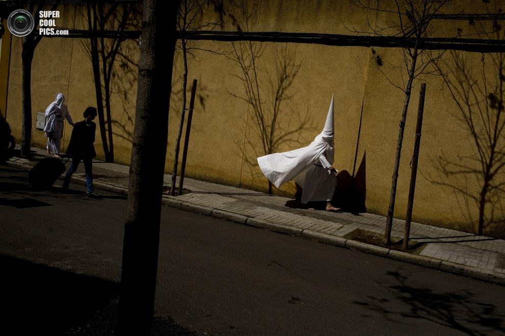 Опаздывающий участник процессии спешит присоединиться к своим собратьям. (AP Photo/Emilio Morenatti)