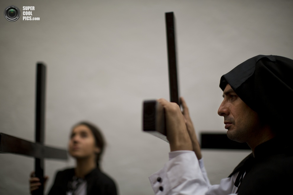 Кающиеся грешники с крестами из братства «Санта-Хеновева». (AP Photo/Emilio Morenatti)