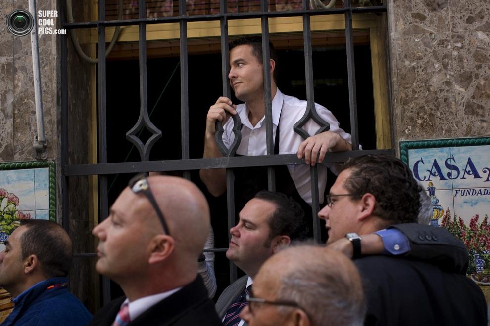 Жители Севильи наблюдают за красочным действом. (AP Photo/Emilio Morenatti)