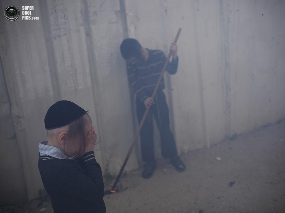 Еврейские дети прикрывают глаза от едкого дыма. (AP Photo/Oded Balilty)