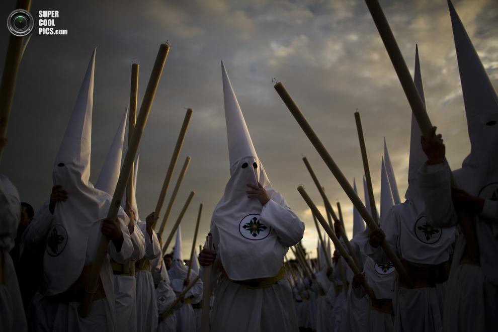 Процессия кающихся грешников братства «Сан-Гонсало» с гигантскими свечами. (AP Photo/Emilio Morenatti)