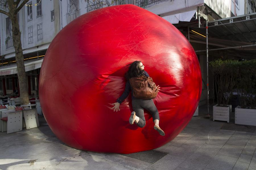 Франция. Париж. 18 апреля. Парижанка взаимодействует с инсталляцией Курта Першке «Красный шар». (EPA/ИТАР-ТАСС/IAN LANGSDON)