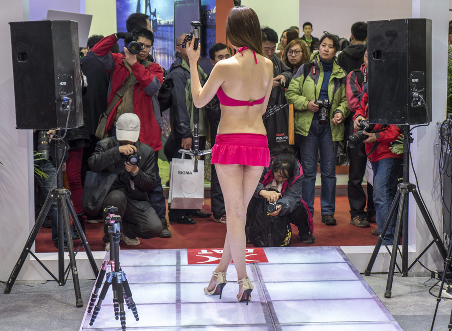 Китай. Пекин. 19 апреля. Модель в купальнике презентует штативы для фотоаппаратов на 16-й Китайской международной выставке фотографических технологий. (EPA/ИТАР-ТАСС/ADRIAN BRADSHAW)