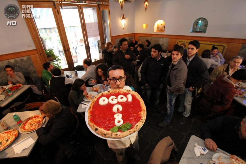 Италия. Неаполь. 3 апреля. Пиццайоло Джино Сорбилло демонстрирует пиццу, которую клиенты его заведения смогут заказать в кредит. (EPA/ИТАР-ТАСС/CESARE ABBATE)