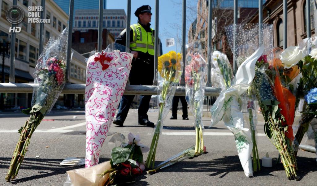 США. Бостон, Массачусетс. 16 апреля. Цветы у кордона полиции близ места теракта на Бостонском марафоне. (EPA/ИТАР-ТАСС/JUSTIN LANE)