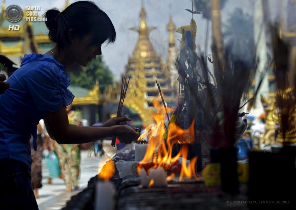 Мьянма. Янгон. 17 апреля. Бирманская девушка зажигает свечи для благовоний во время новогодних молитв у Пагоды Шведагон. (EPA/ИТАР-ТАСС/LYNN BO BO)