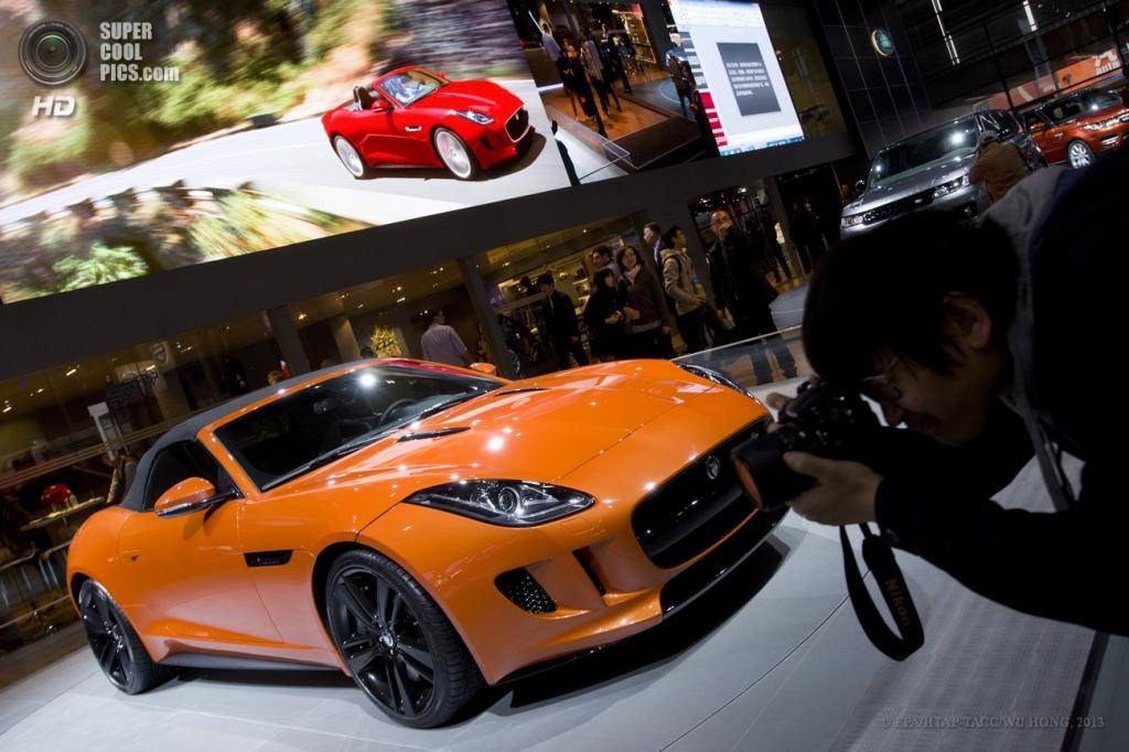 Китай. Шанхай. 21 апреля. Посетитель 15-ой Шанхайской международной выставки автомобильной индустрии снимает новый родстер Jaguar F-Type. (EPA/ИТАР-ТАСС/WU HONG)