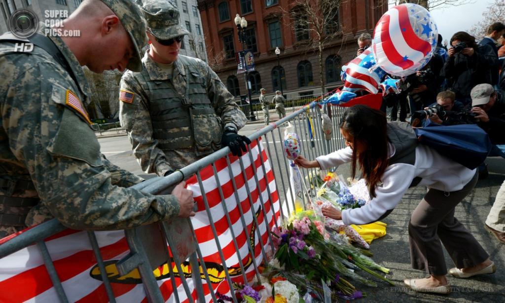 США. Бостон, Массачусетс. 16 апреля. Девушка вешает воздушный шарик на ограждение, охраняемое гвардейцами, близ места теракта на Бостонском марафоне. (EPA/ИТАР-ТАСС/JUSTIN LANE)