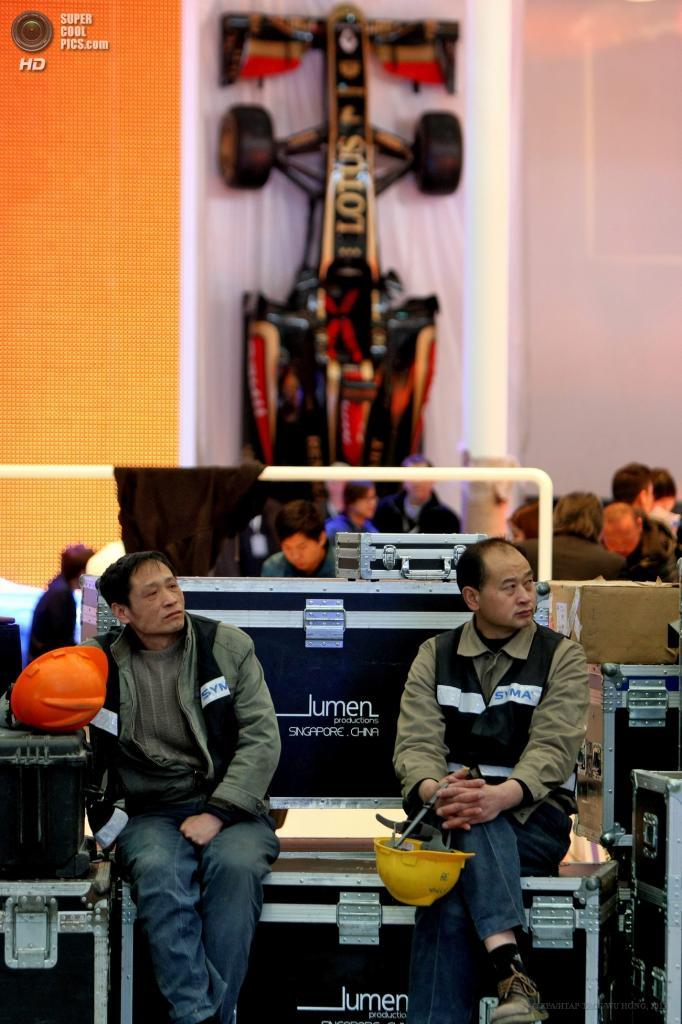Китай. Шанхай. 21 апреля. Работники выставки отдыхают на скамейке на фоне болида «Формулы-1» команды Lotus. (EPA/ИТАР-ТАСС/WU HONG)
