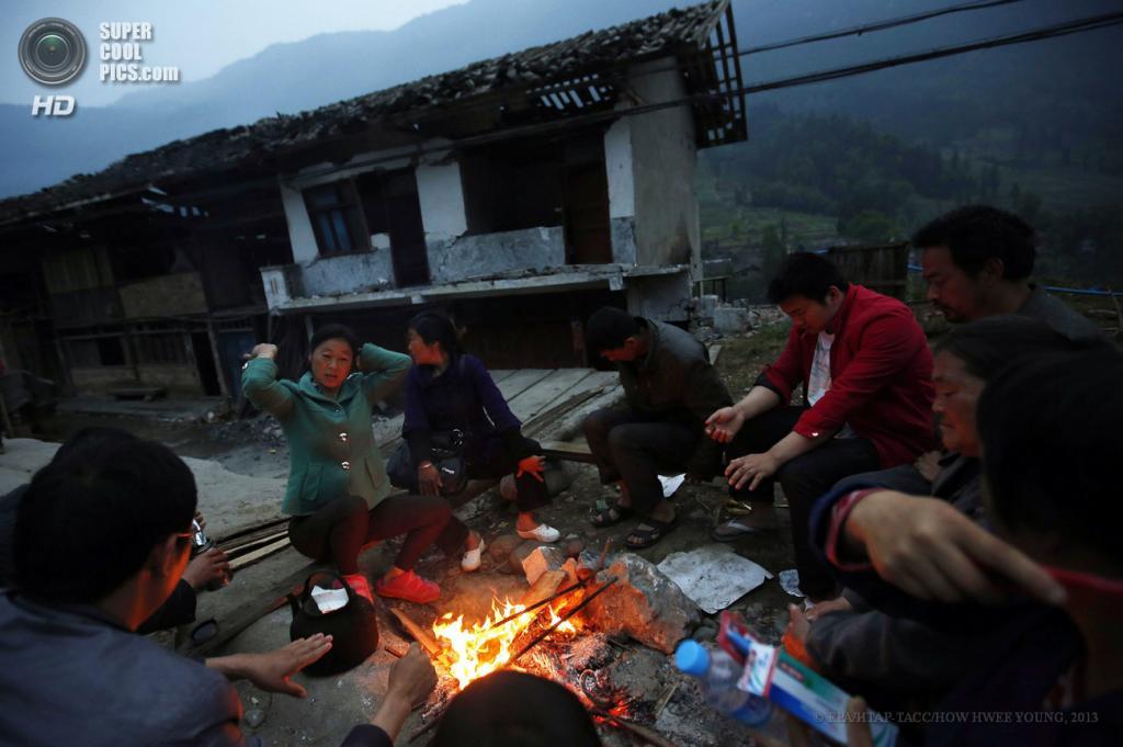 Китай. Сычуань. 23 апреля. Люди, лишившиеся своих домов, греются у костра. (EPA/ИТАР-ТАСС/HOW HWEE YOUNG)