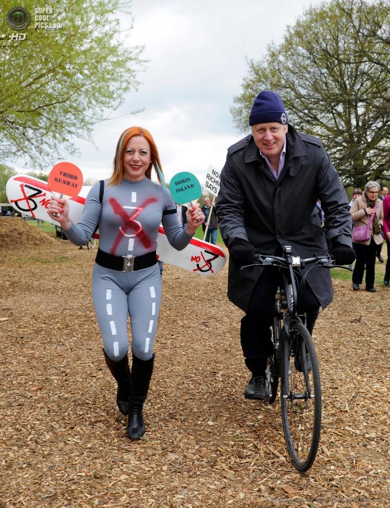 Англия. Лондон. 27 апреля. Мэр Лондона Борис Джонсон на велосипеде с демонстрантом в костюме взлётной полосы на акции протеста против расширения аэропорта «Хитроу». (EPA/ИТАР-ТАСС/FACUNDO ARRIZABALAGA)