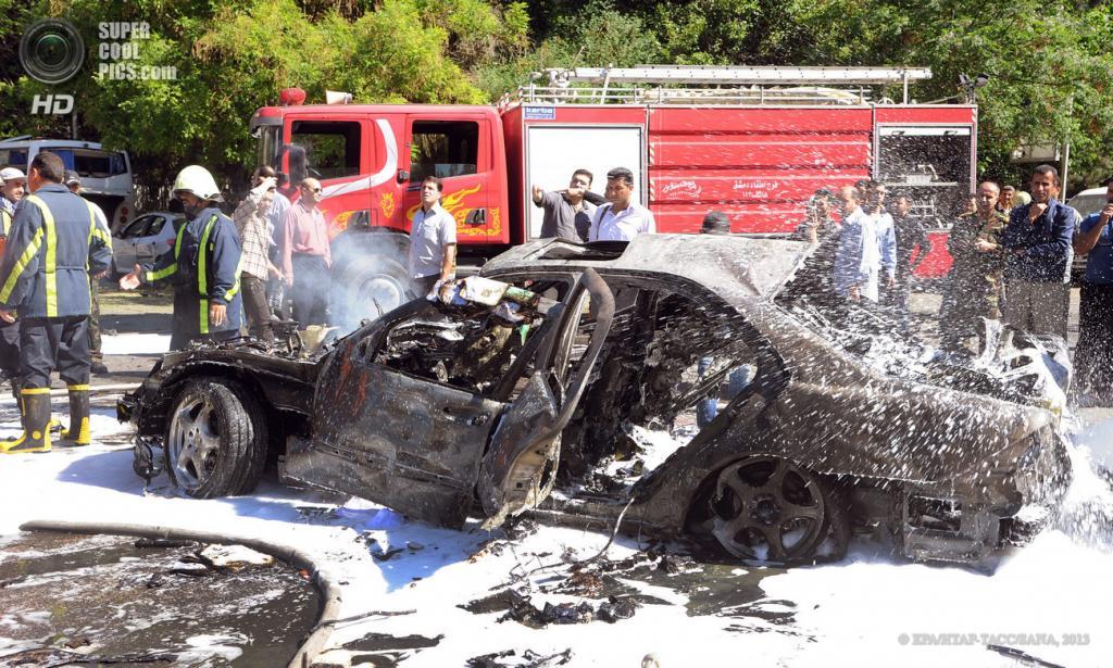 Сирия. Дамаск. 29 апреля. Работа пожарных на месте подрыва машины возле кортежа премьер-министра Сирии Ваиля аль-Халки. (EPA/ИТАР-ТАСС/SANA)