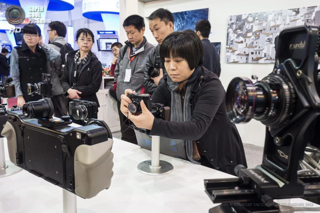 Китай. Пекин. 19 апреля. Посетительница оценивает оборудование Roundshot. (EPA/ИТАР-ТАСС/ADRIAN BRADSHAW)