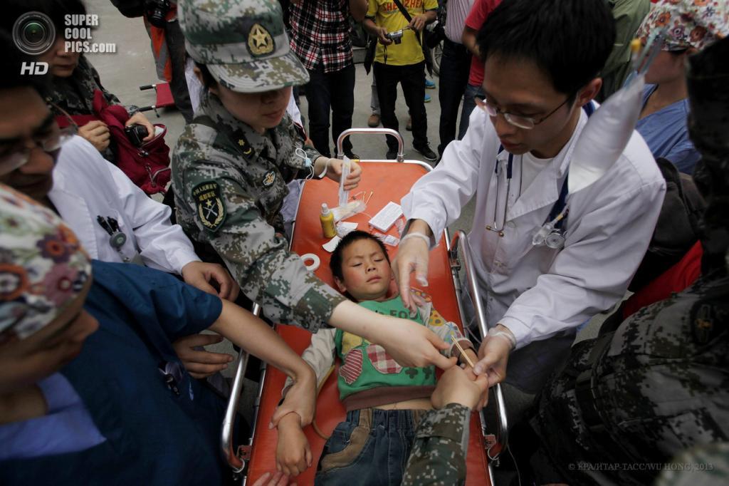 Китай. Яань, Сычуань. 21 апреля. Оказание помощи пострадавшему ребёнку. (EPA/ИТАР-ТАСС/WU HONG)