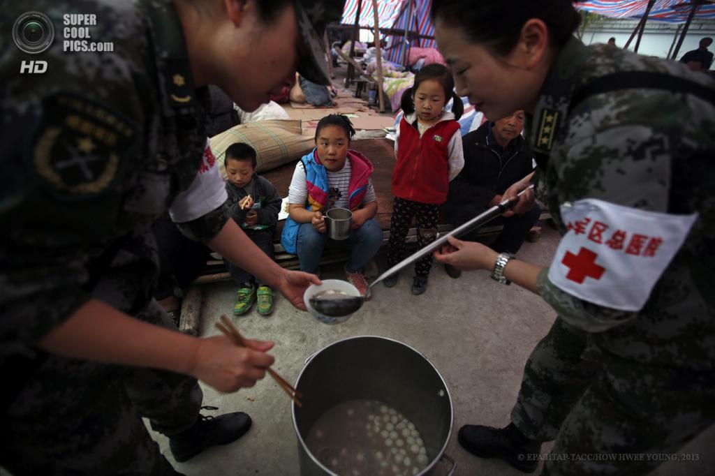 Китай. Сычуань. 23 апреля. Медицинский работник раздает людям юшку с пельменями. (EPA/ИТАР-ТАСС/HOW HWEE YOUNG)