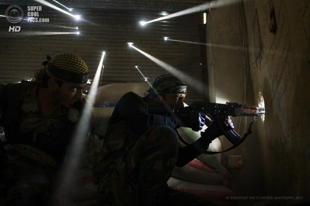 Сирия. Алеппо. 18 октября 2012 года. Сирийские боевики в засаде, стены которой испещрены дырами от пуль. (EPA/ИТАР-ТАСС/JAVIER MANZANO)