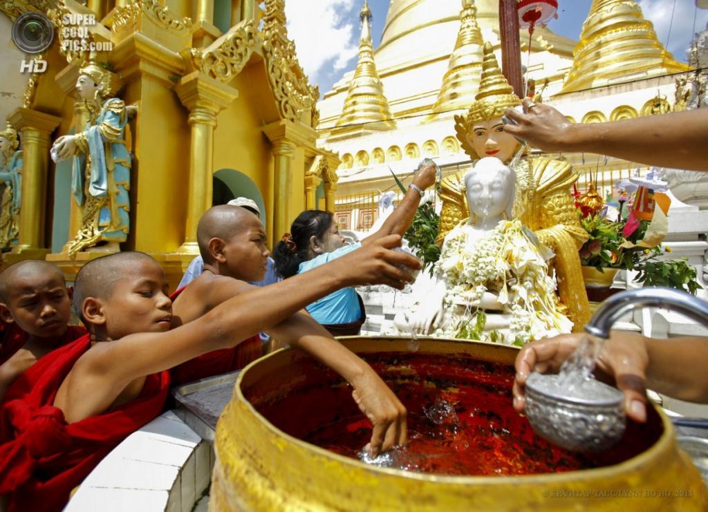 Мьянма. Янгон. 17 апреля. Молодые буддийские монахи обливают водой статую Будды. (EPA/ИТАР-ТАСС/LYNN BO BO)