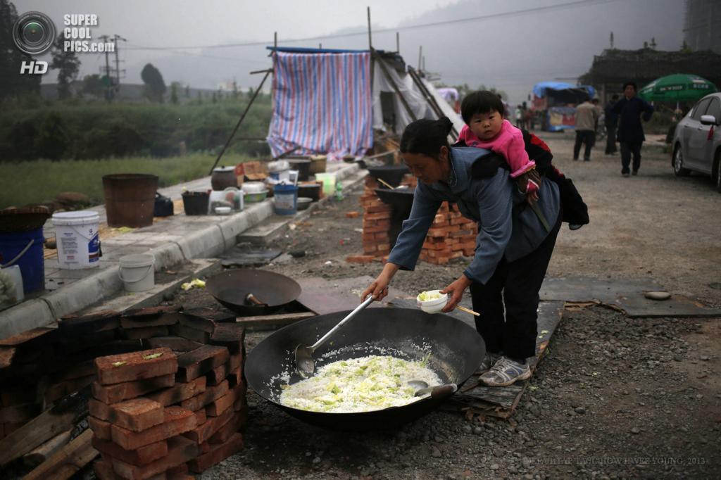 Китай. Яань, Сычуань. 22 апреля. Мама с маленькой дочкой набирает рис на обед во временном лагере для пострадавших. (EPA/ИТАР-ТАСС/HOW HWEE YOUNG)