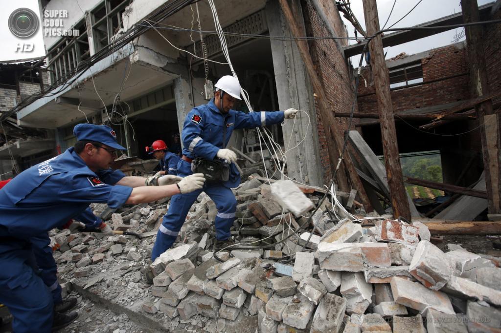 Китай. Сычуань. 23 апреля. Спасатели работают на развалинах домов. (EPA/ИТАР-ТАСС/HOW HWEE YOUNG)
