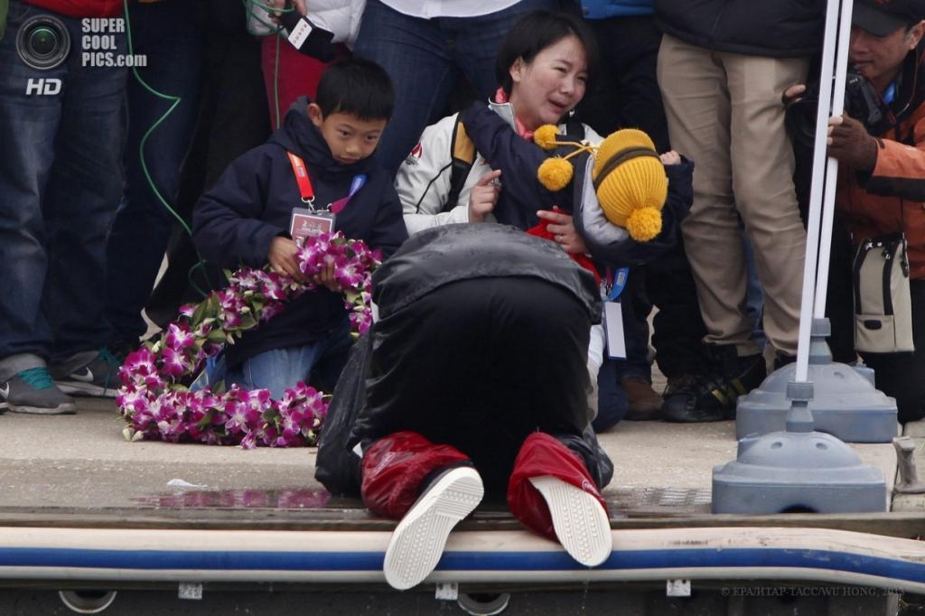 Китай. Циндао, Шаньдун. 5 апреля. Моряк склонился перед женой и сыновьями. (EPA/ИТАР-ТАСС/WU HONG)