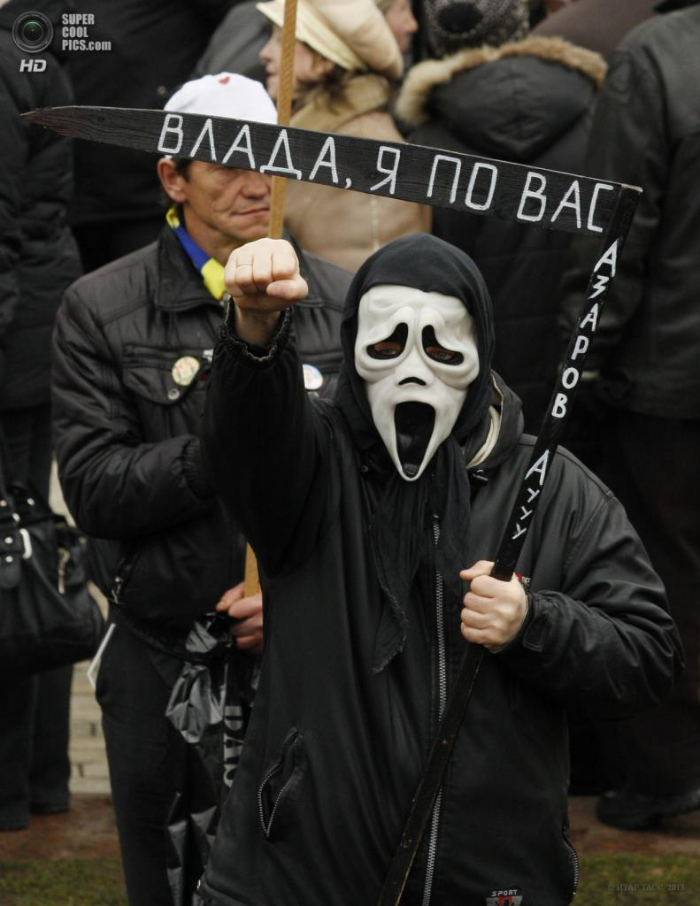 Украина. Киев. 7 апреля. Участники митинга оппозиции «Вставай, Украина!» в костюме смерти с надписью «Власть, я за вами. Азаров, аууу» на деревянной косе. (ИТАР-ТАСС)