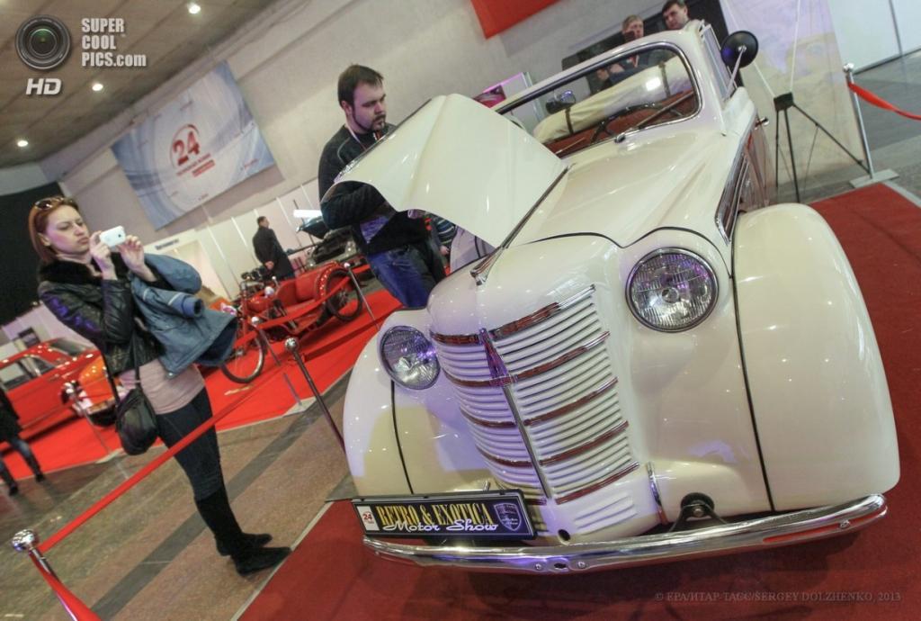 Украина. Киев. 12 апреля. Посетительница делает снимки Москвич-400 на выставке VII Retro & Exotica Motor Show. (EPA/ИТАР-ТАСС/SERGEY DOLZHENKO)