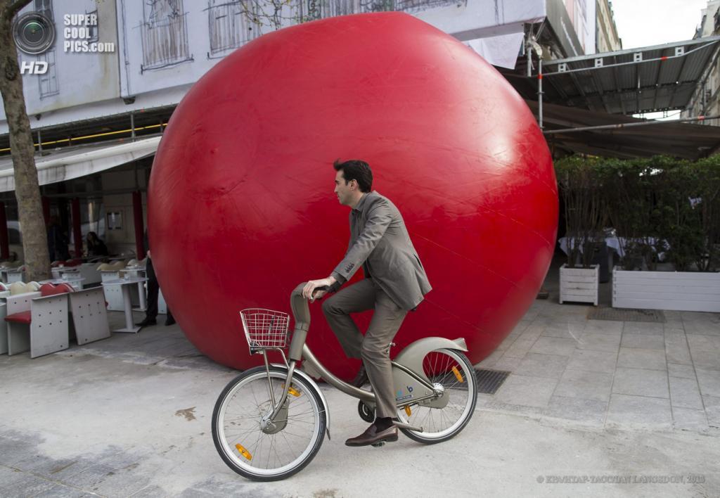 Франция. Париж. 18 апреля. Парижанин на велосипеде у инсталляции Курта Першке «Красный шар». (EPA/ИТАР-ТАСС/IAN LANGSDON)