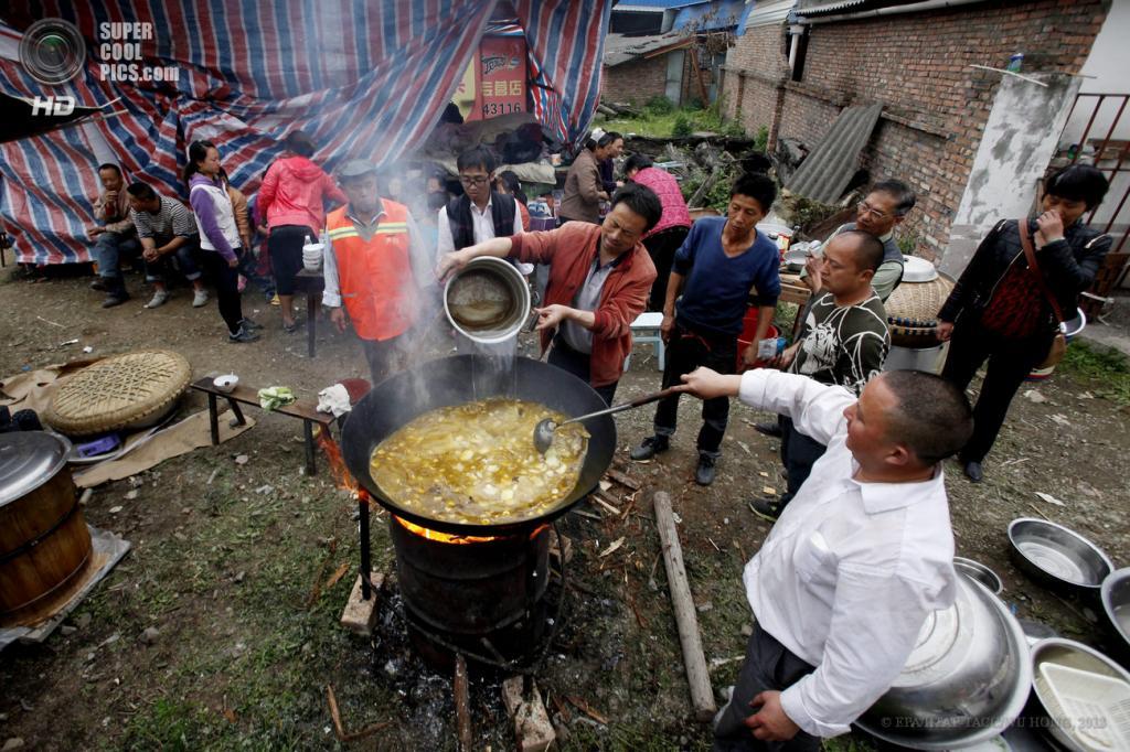 Китай. Яань, Сычуань. 21 апреля. Жители домов, разрушенных при землетрясении, готовят еду. (EPA/ИТАР-ТАСС/WU HONG)