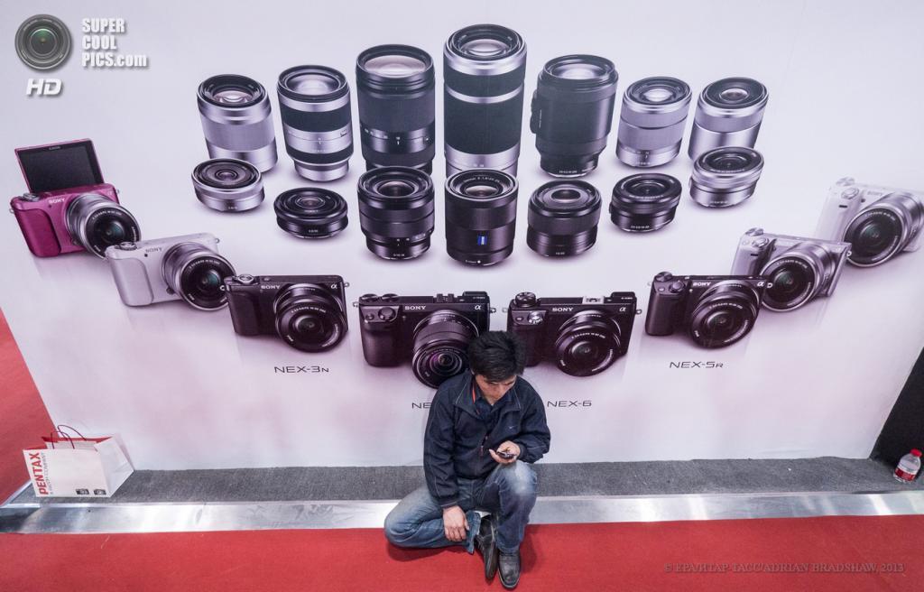 Китай. Пекин. 19 апреля. Посетитель отдыхает у рекламного постера Sony. (EPA/ИТАР-ТАСС/ADRIAN BRADSHAW)